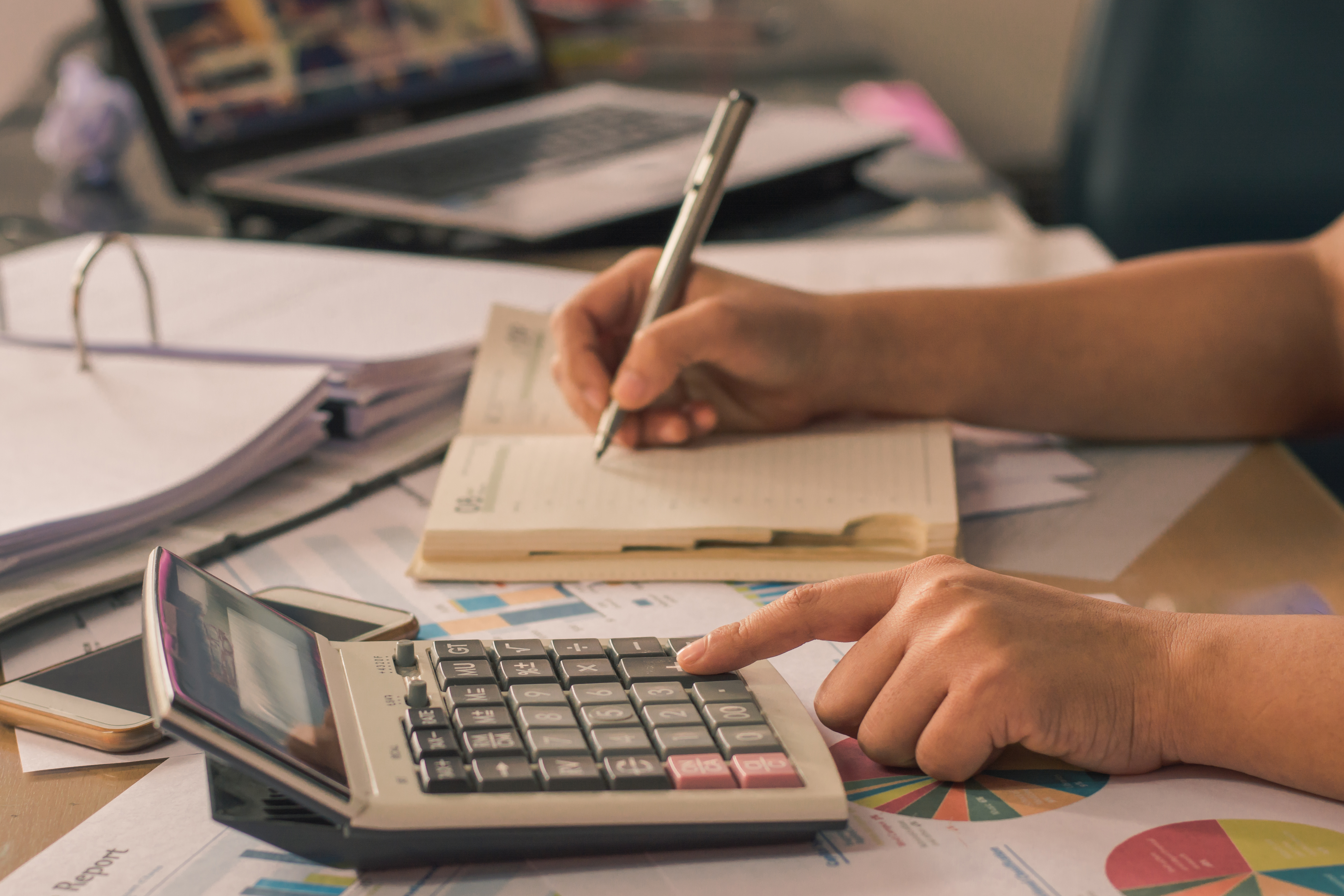 person reviewing drama theatre budget documents with calculator and notes
