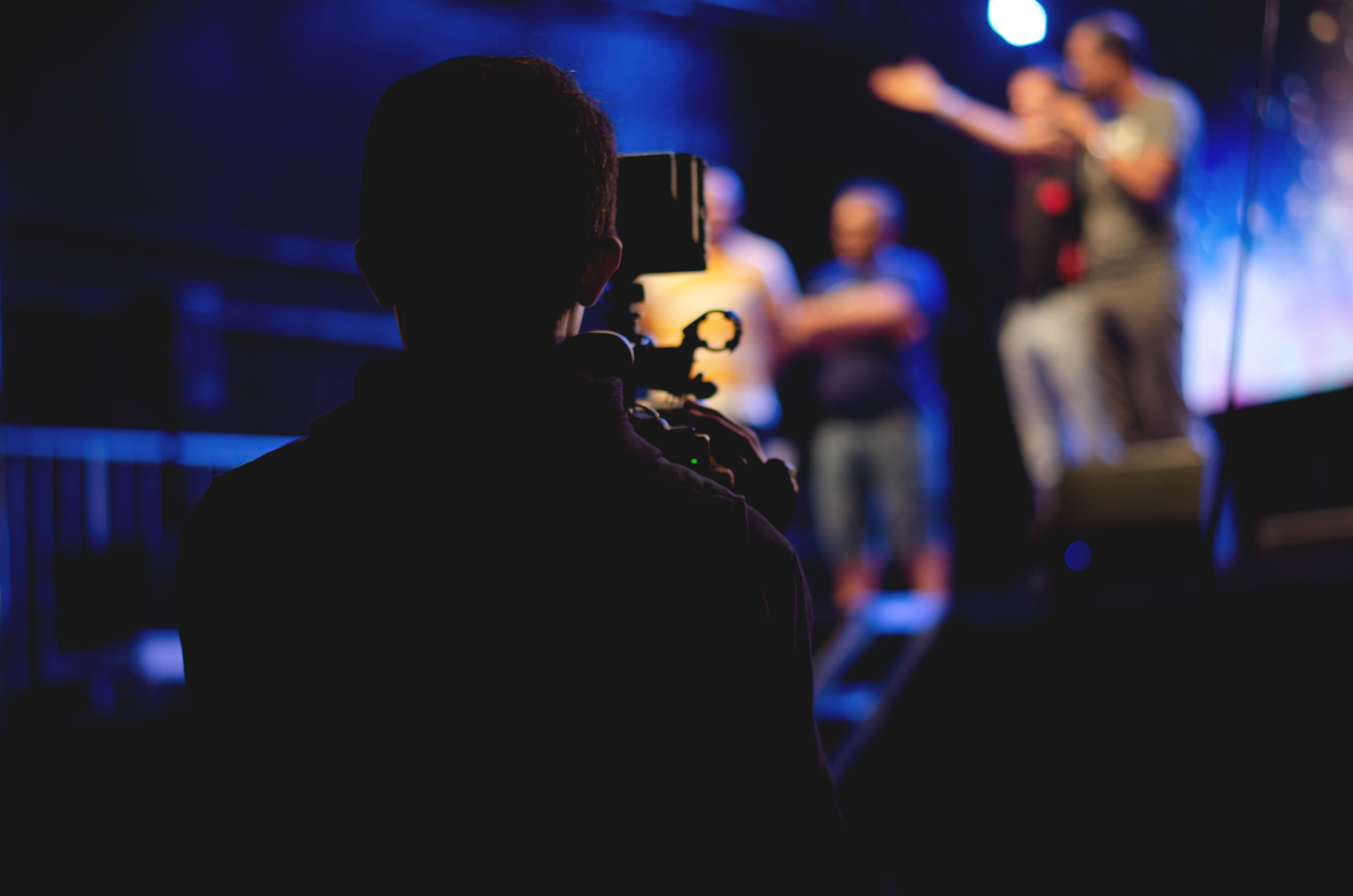 person filming stage play for theatre online streaming virtual performance